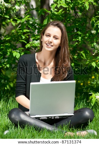 Lovely young woman sitting on grass in park and using laptop