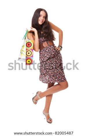 lovely young woman standing with shopping bags on shoulder isolated on white background - stock photo