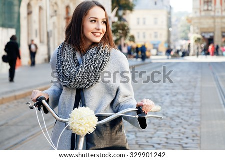 Lovely young woman, wearing in gray jacket and scarf, with black bag, posing with bike on the street of old European city, on sunny day, waist up - stock photo