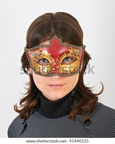 Lovely young woman with carnival mask on her face - stock photo