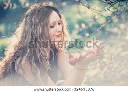 Lovely young woman with long wavy hair in the spring beautiful garden among the blossoming magnolias, closeup