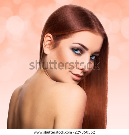 Lovely young woman with perfect straight brown hair with blue eyes looking at camera in studio on abstract orange background - stock photo