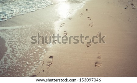 Lover footprints on the beach at sunset time in vintage style - stock photo