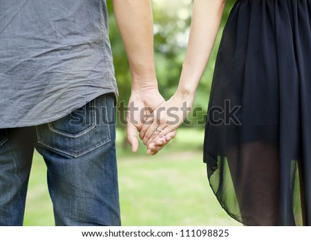 Lovers couple holding hands in the park