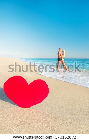 Lovers embrace couple at sea beach and big red heart - St. Valentines Day concept - stock photo