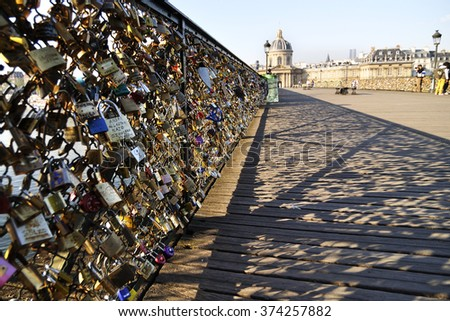 Lovers have locked thousands of locks to the Pont des Arts bridge in Paris. The padlocks, with keys thrown into the Seine River, is a modern tradition - stock photo