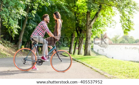 lovers having a deep eye contact, smiling and touching their hands, standing on a bike on a beautiful summer day - stock photo