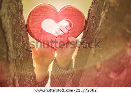 lovers holding a stylized heart in hands - stock photo