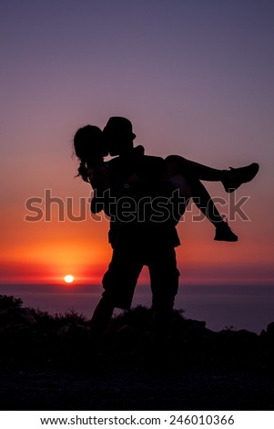 Lovers kiss under sunset of Crete
