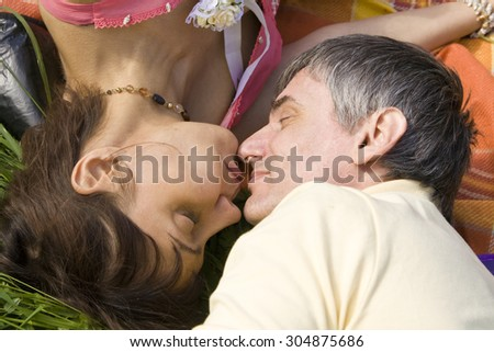 Lovers laying on grass and kissing each other (heads only). - stock photo