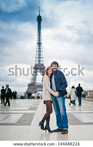 Lovers look at camera in Paris with the Eiffel Tower in the Background