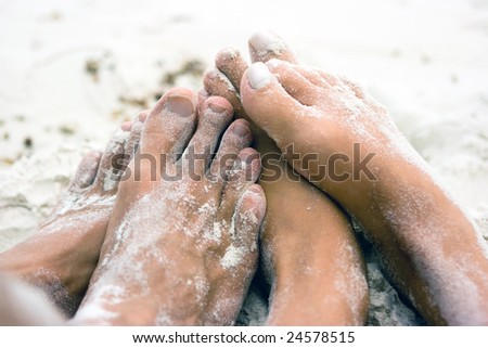 Lovers lying on the beach but we see only their feet