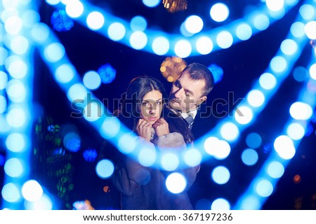 Lovers man and woman in park with evening lights. - stock photo