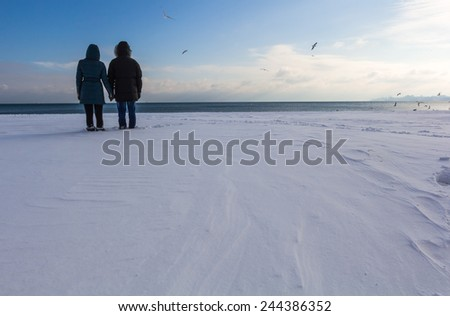 Lovers on a walk on the banks of the winter sea - stock photo