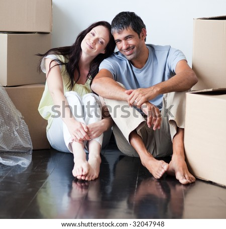Lovers sitting on the floor of their new house - stock photo