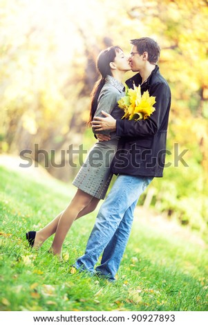 Lovers spend sunny day in the autumn park, they kiss while holding a bouqet of autumn leaves - stock photo