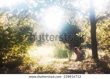 Lovers under tree. Romantic relationship, first love. Forest landscape with large tree. Backlight - stock photo