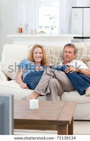 Lovers watching tv in the living room at home - stock photo