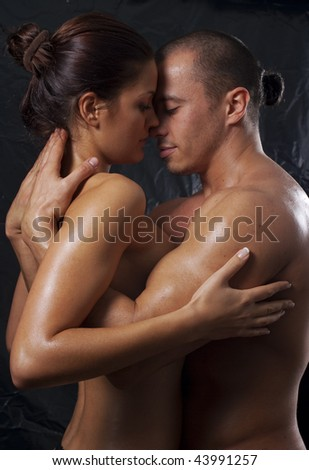 Loving affectionate nude heterosexual couple engaging in sexual games, hugging and kissing