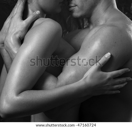 Loving affectionate nude heterosexual couple engaging in sexual games, hugging and kissing - stock photo