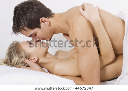 Loving affectionate nude heterosexual couple on bed in affectionate sensual kiss. - stock photo