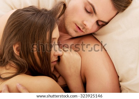 Loving affectionate nude heterosexual couple relaxing in bed.
