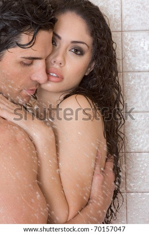 Loving affectionate nude young heterosexual couple in affectionate sensual kiss after taking shower. Mid adult Caucasian men in late 30s and young Latina woman in early 20s - stock photo