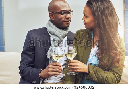 Loving African American couple in a close embrace toasting each other with white wine as they look deeply into each others eyes - stock photo