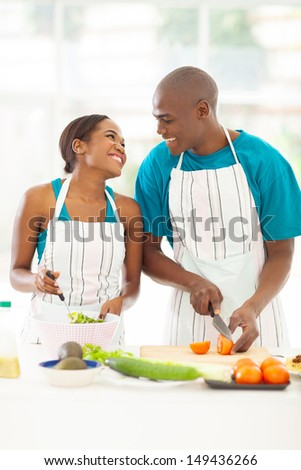 loving afro american couple preparing green salad in kitchen - stock photo