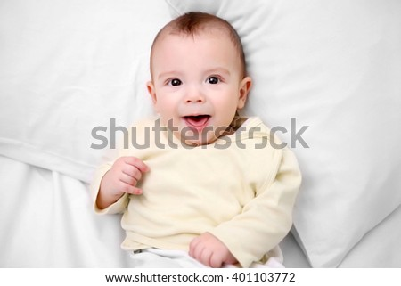Loving baby lying on soft bed, close up - stock photo