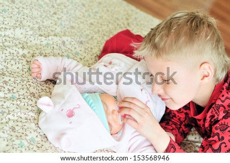 loving brother with newborn sister at home - stock photo