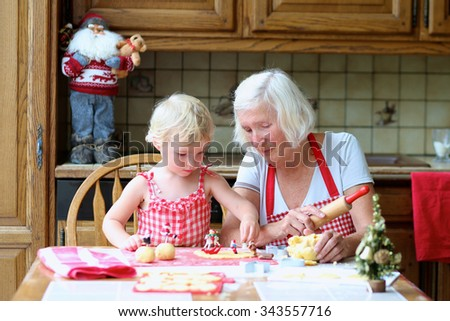 Loving caring grandmother, beautiful senior woman, baking tasty sweet cookies together with her granddaughter, cute little toddler girl, sitting at the table in classic traditional wooden kitchen