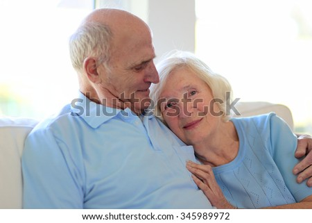 Loving caring senior couple relaxing at home sitting on sofa. Mature husband and wife spending time together, hugging and kissing. - stock photo