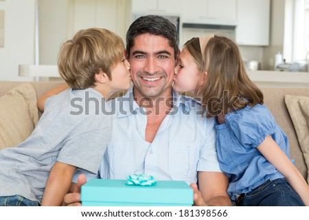 Loving children kissing on fathers cheeks at home - stock photo
