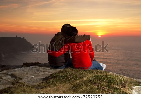 Loving Couple at sunset on irish Cliffs of Moher - stock photo