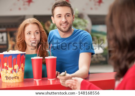 Loving couple at the restaurant. Young loving couple buying popcorn and soda at the cinema bar - stock photo