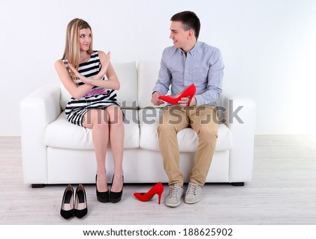 Loving couple choose new shoes, on light background - stock photo