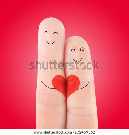 loving couple concept with big valentine heart, painted at fingers against red gradient background