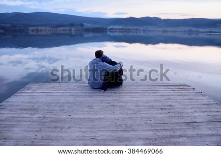 Loving couple couple hugging each other near by sea during calm sunset - stock photo