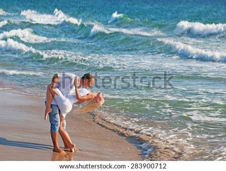 loving couple dancing at sand on sea beach at summer against waves surf - stock photo