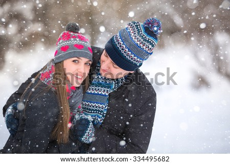 Loving couple embracing in winter park. They put colored caps and scarves. Loving warm hands to each other. Copy space. The girl hat with red hearts, it looks in the picture. - stock photo