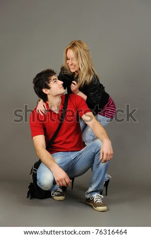 Loving couple embracing on gray background.