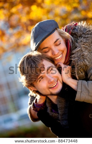 Loving couple enjoying their autumn romance at the park - stock photo