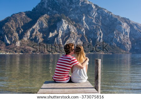 Loving couple giving a kiss on the pier at the lake in the Austrian Alps - stock photo