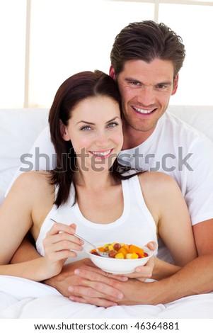 Loving couple having breakfast lying in the bed - stock photo