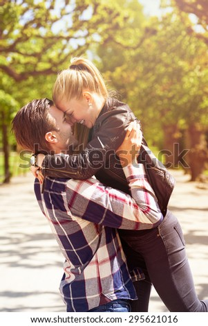 Loving couple having fun in the park as the man lifts his girlfriend, wife or partner into the air so that their foreheads touch, both are smiling and looking into each others eyes with emotion - stock photo