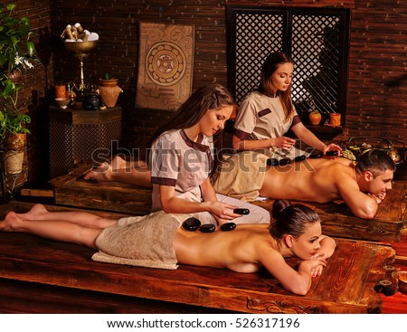 Loving couple having stone massage in indian Ayurveda Spa salon. Man and woman lie on the wooden benches decorated with Indian ornaments. Ayurveda lastone spa treatment.