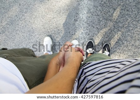 Loving couple holding hands and standing on the edge - stock photo