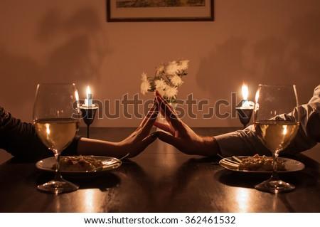 Loving couple holding hands during romantic dinner - stock photo