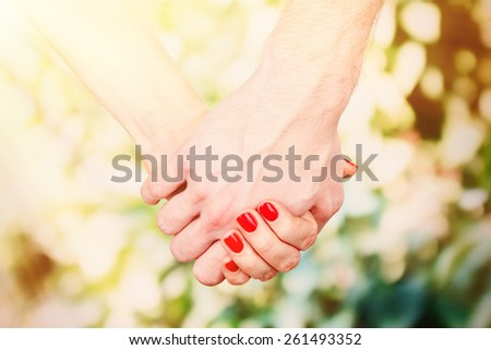 Loving couple holding hands outdoors - stock photo